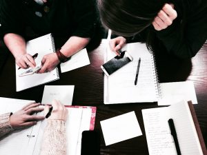 group of people with their notepads out studying