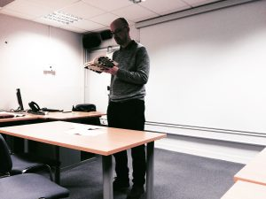 man standing in front of classroom with book