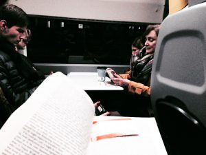 someone reading and a group of friends in a train in the background